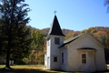 A small country church in the middle of the West Virginia mountains with fall foliage in the background during an Autumn day.