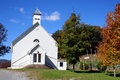 A beautiful little white church with three crosses on a hill. The leaves on the trees are changing as fall approaches.