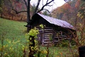 Rustic old country shed with the scenic colors of the fall leaves covering the trees in the hills.