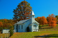 A very quaint and simple country church surrounded by fall foliage under a clear blue sky. Little white churches like this one are becoming few and far between. We found this little church next to the road in the mountains of West Virginia. Across the road was a beautiful apple tree with some of the biggest red apples you have ever seen, and they were so good!